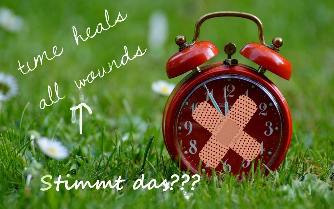 """Foto: Wecker auf dem Rasen mit Pflaster kreuzweise aufgeklebt. Text: """"Time heals all wounds"""" Ein Pfeil dorthin mit Text """"Stimmt das???"""""""
